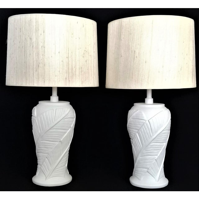 Offering a striking vintage pair of SOLID white plaster palm tree or banana leaf lamps, circa 1980s. These lovely tropical...