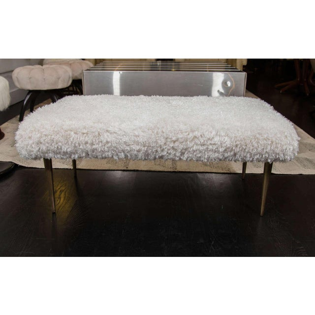 Faux Mongolian lamb fur covered Mid-Century bench. Wood frame with brass base.