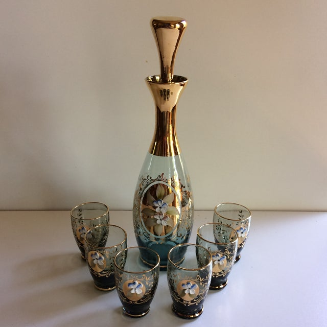 Wonderful vintage Bohemian Blown glass decanter set has 6 glasses with gold and flower appliqué. The decanter also has...