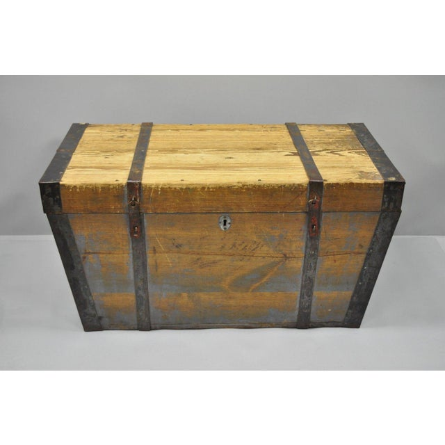This is an antique primitive style flat top wooden trunk/blanket chest. The late 19th century piece features iron & steel...