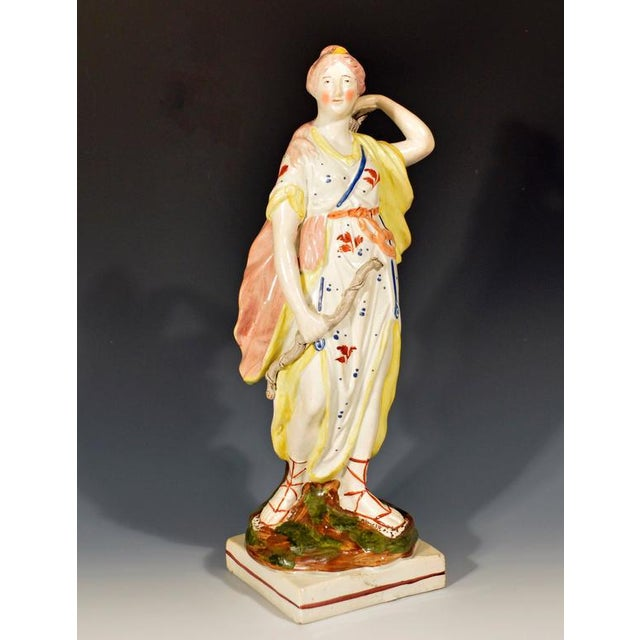 The Staffordshire pearlware figure is either made by Ralph Wood Jr.. or Enoch Wood. The figure with overglaze enamel...