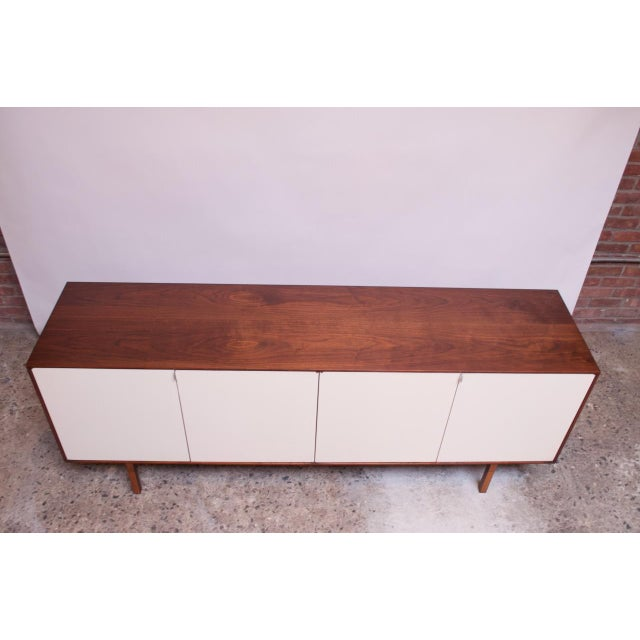 Credenza / cabinet (Model #541, circa 1952) designed by Florence Knoll for Knoll Associates composed of a walnut frame and...