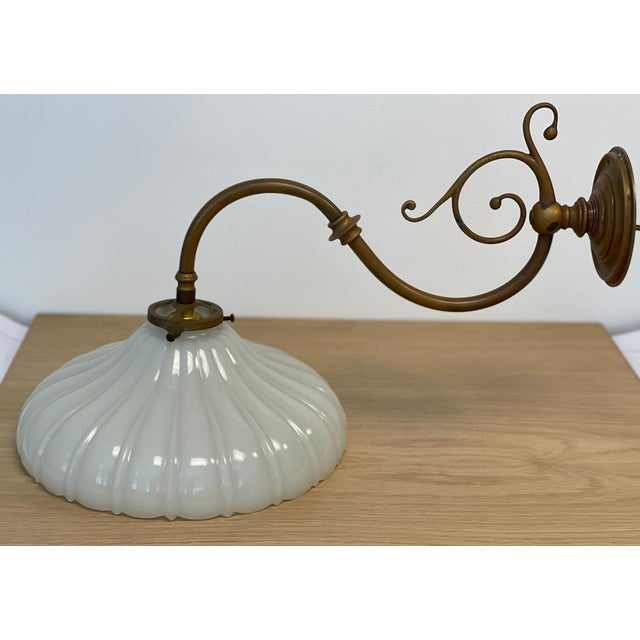 """Vintage Wall Sconce in Antiqued Brass With Ribbed Scalloped Milk Glass Shade. Overall dimensions: 11""""W x 19""""D x 12""""H Glass..."""