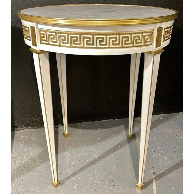 Pair of Bouillotte / end tables. Each having bronze framed white marble tops supported a white base with a Greek key...