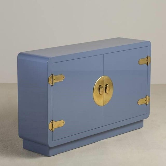 Slender console cabinet by Mastercraft. Newly lacquered in a soft blue with brass trim at the top and sides of the...