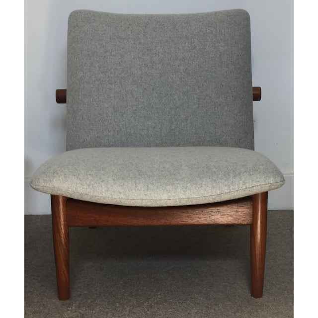 Finn Juhl's iconic 'Japan' chair with teak frame, wonderful exposed brass brackets and floating seat. The unusual frame...