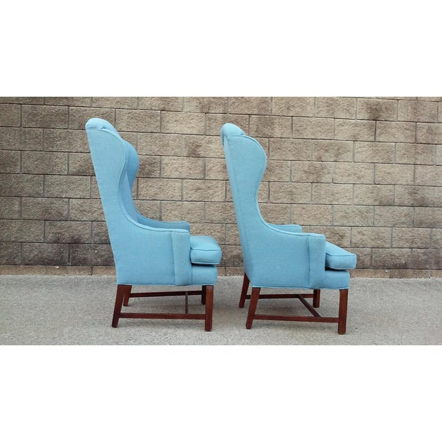A pair of stunning Mid Century high back arm chairs with great lines. Newer blue upholstery, solid frames, slight wear to...