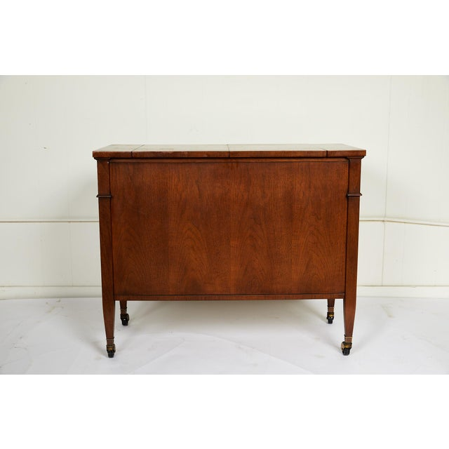 This 20th century vintage sideboard features a walnut finish on all sides, convertible black formica top, and casters for...