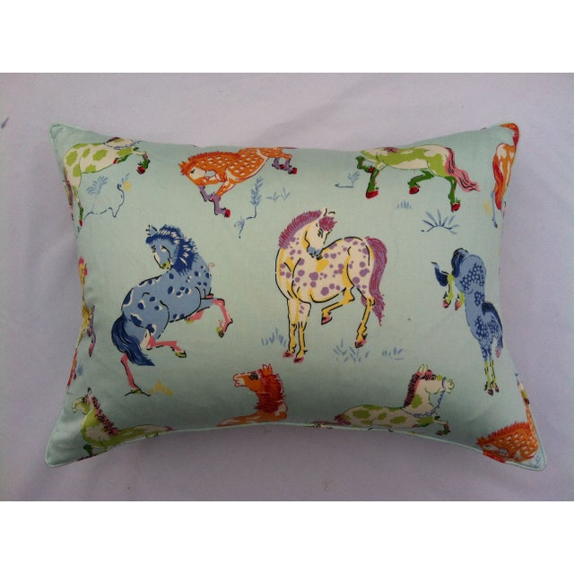 A pair of throw pillows in a colorful horse fabric. The graphic fabric features bright colors. The pillows have a small...