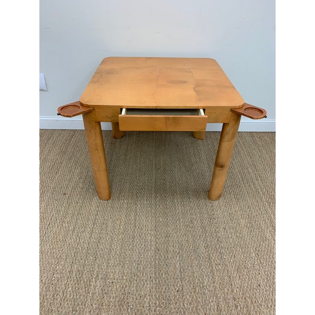 A rare table in the style of Karl Springer, beautifully covered in lacqured goatskin with pull-out coasters at each corner.