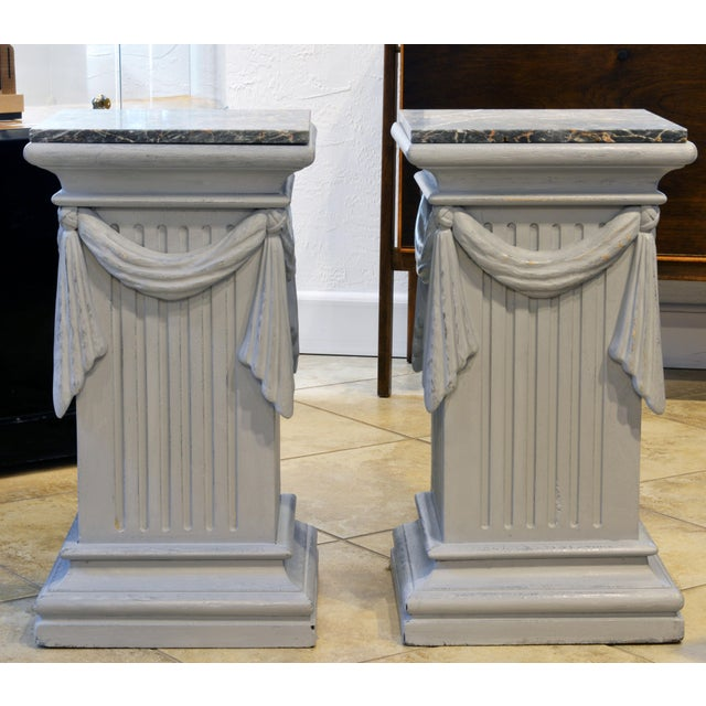 This pair of neoclassical Gustavian style carved and gray painted pedestals are equally useful as lamp tables or end...