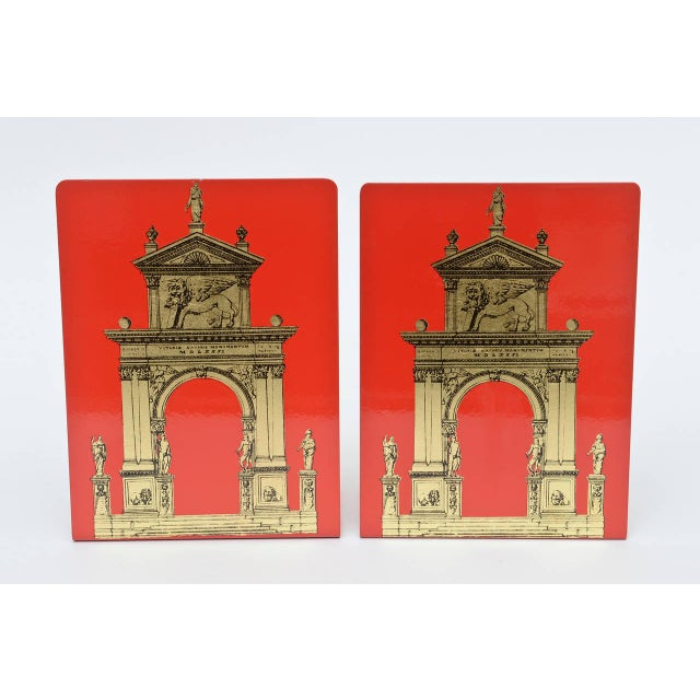 These arresting Fornasetti bookends with their vibrant red and classical gilded roman architecture ring book lovers. The...