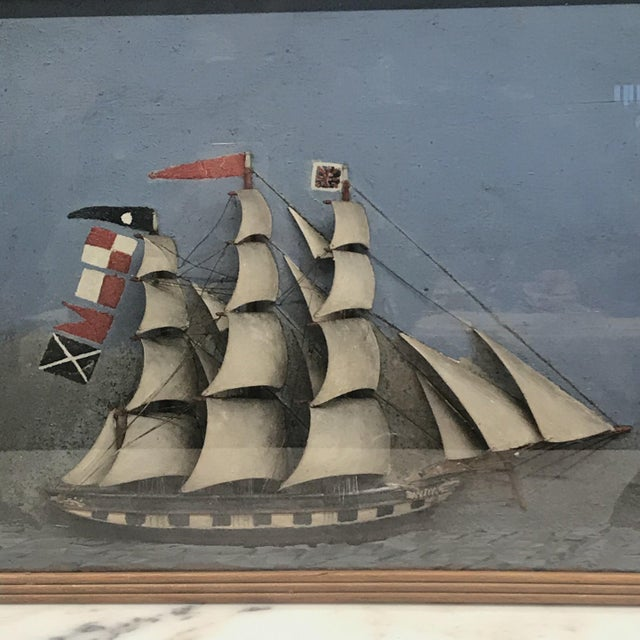 Stunning ship diorama of a three mast schooner with carved wooden hull, sails, and masts, mounted in a deep mitered wood...