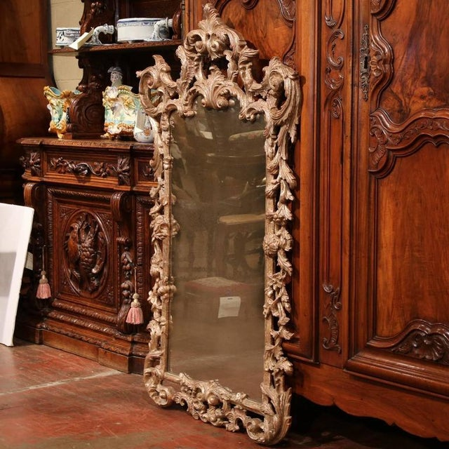 This ornate, mid-century carved mirror was crafted in Italy, circa 1960. The frame around the mirror is embellished with...