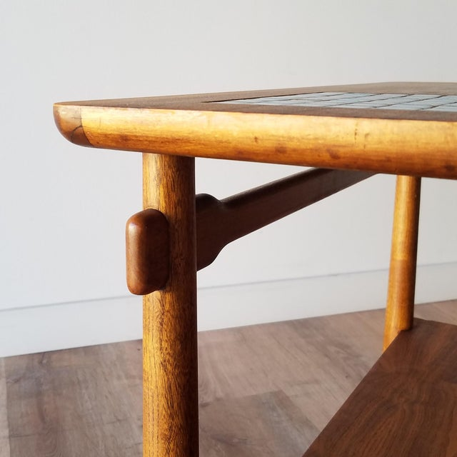 A two-tiered walnut side table with a mosaic tile inlay made by Lane. This table features a lower shelf, inverse tapered...