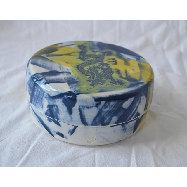 This Asian inspired porcelain ceramic box is thrown on the potters wheel and decorated with layers of slip, underglazes...