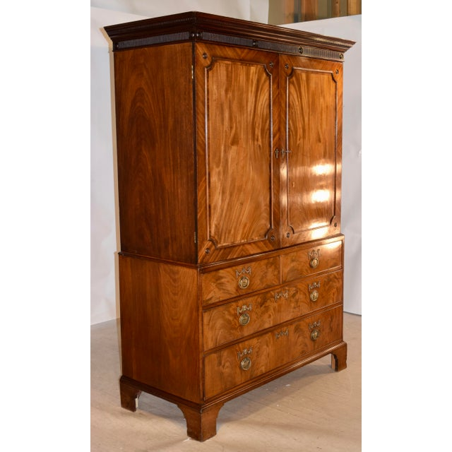 Georgian linen press made from beautifully figured mahogany. The top is finished with a substantial crown over fluted...