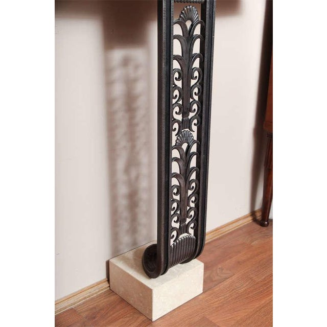 Modern Art Deco style console in the manner of Edgar Brandt. Wrought iron, with travertine top and base. Measures: Height...