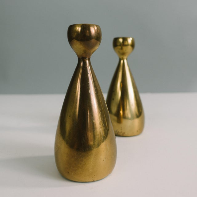This is a pair of candlestick holders designed by Ben Seibel for jenfred-ware. They are heavy, made of brass and have felt...