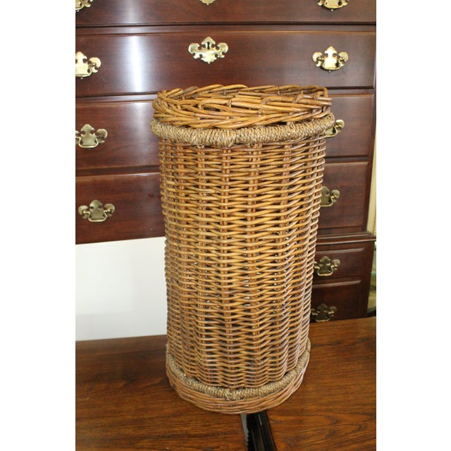Tall cylindrical shaped brown wicker hand made basket.
