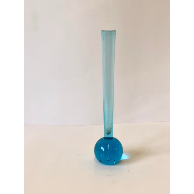 Mid-Century modern bud or stem vase of blue art glass with a controlled bubble paperweight base below a slim tapered...