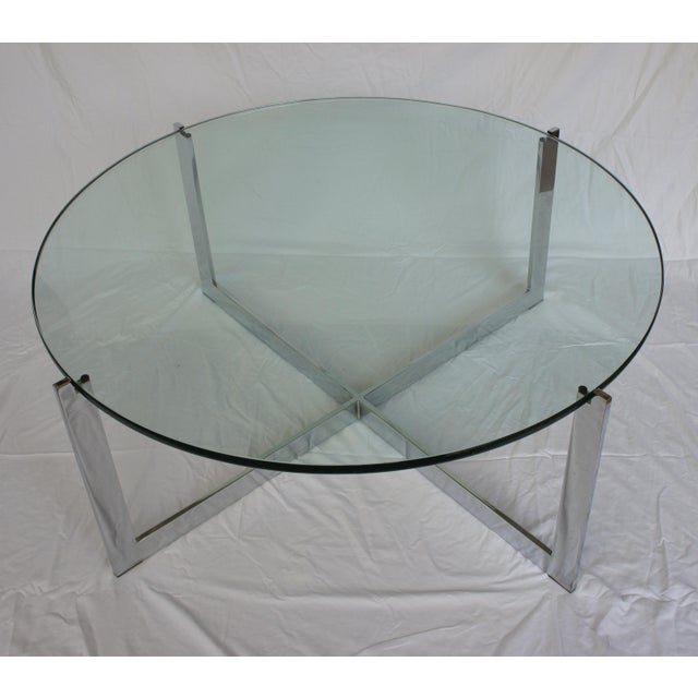Chrome and glass round x-base coffee table, designed by Milo Baughman. Heavy and substantial 3/4 in thick glass top....