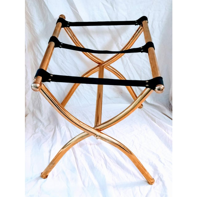A vintage brass folding luggage rack. The solid brass frame has a curve design to the legs with ball accents and feet....