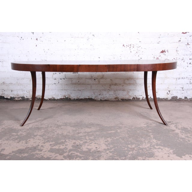 A rare and exceptional mid-century modern saber leg walnut extension dining table By T.H. Robsjohn-Gibbings for Widdicomb...