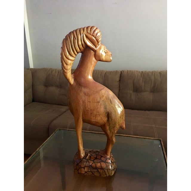 This huge Ram was painstakingly hand carved from a single piece of wood. It is in great condition with a crack in one side...