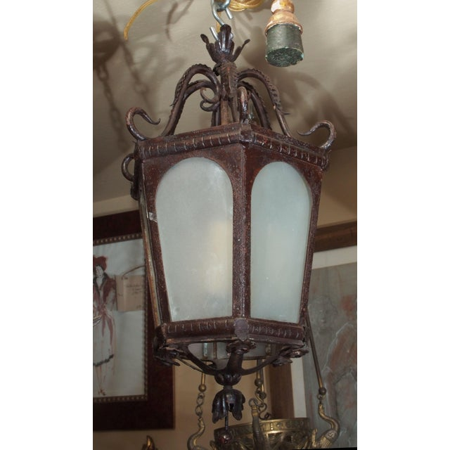 Mid 20th century Iron Lantern with milk glass panels. Scrolled crown, hexagonal shape, wired with a 3 light cluster....