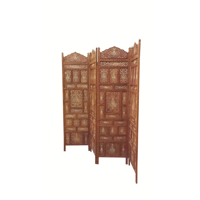 A richly carved Indian wooden screen with four panels. Heavy and made of hardwood, each panel consists of twelve smaller...