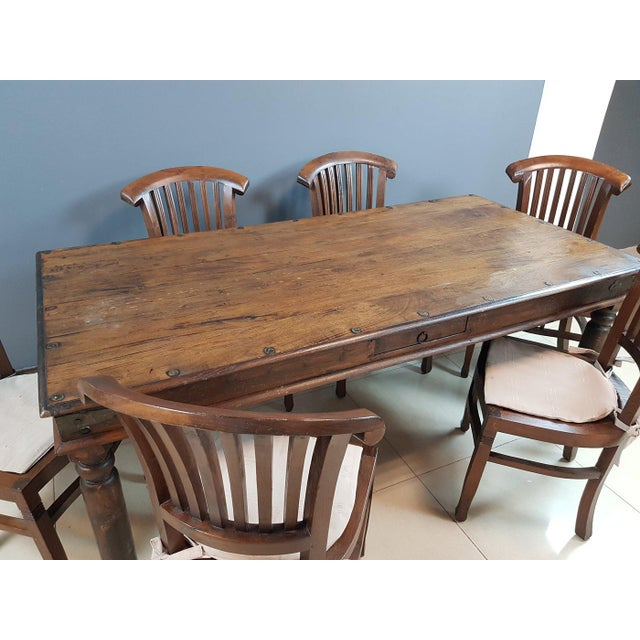 Large vintage Indian handmade colonial style dining set table and 6 chairs. This colonial dining table set has aged...