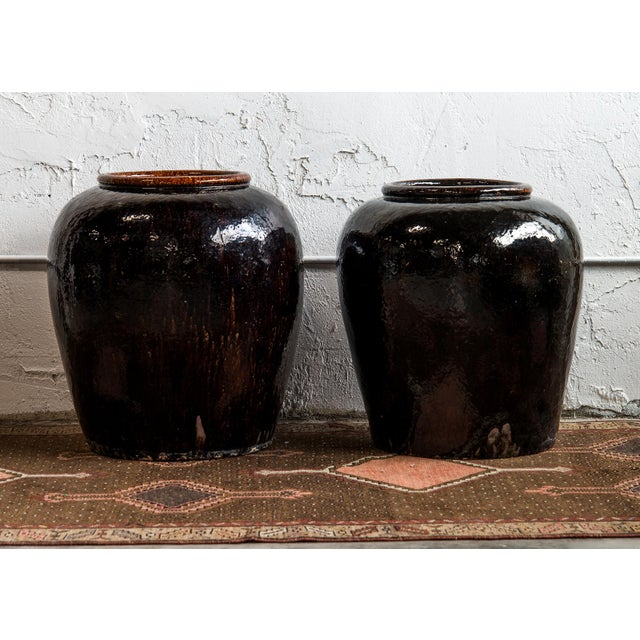 Near Pair of Vintage Chinese Glazed Black Ceramic Pots, originally used in Shanxi Province for vinegar storage and...