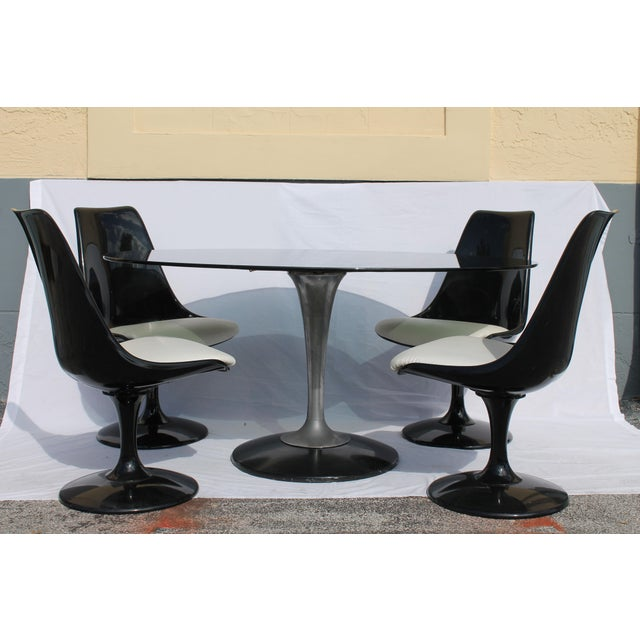 A spectacular 1960's Knoll style 5 piece dining set, including 4 refinished, black gloss, Tulip form, scoop back, heavy...