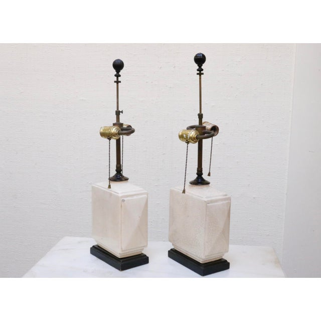 A pair of petite antique lamps decorated in a white craquelure glaze. Opposing sockets turn on and off with fine pull...