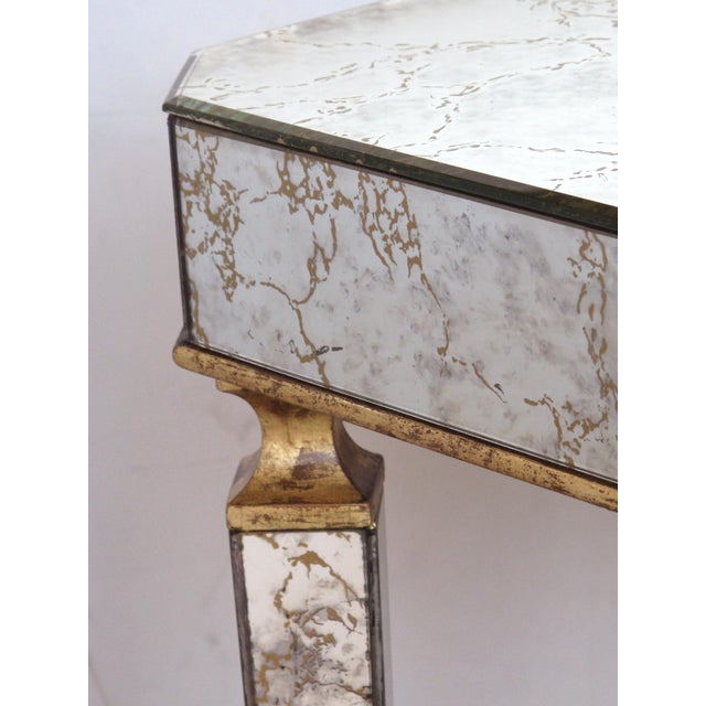 the rectangular top with canted corners raised on tapering quadrangular supports; veneered with mirrored plates with gold...