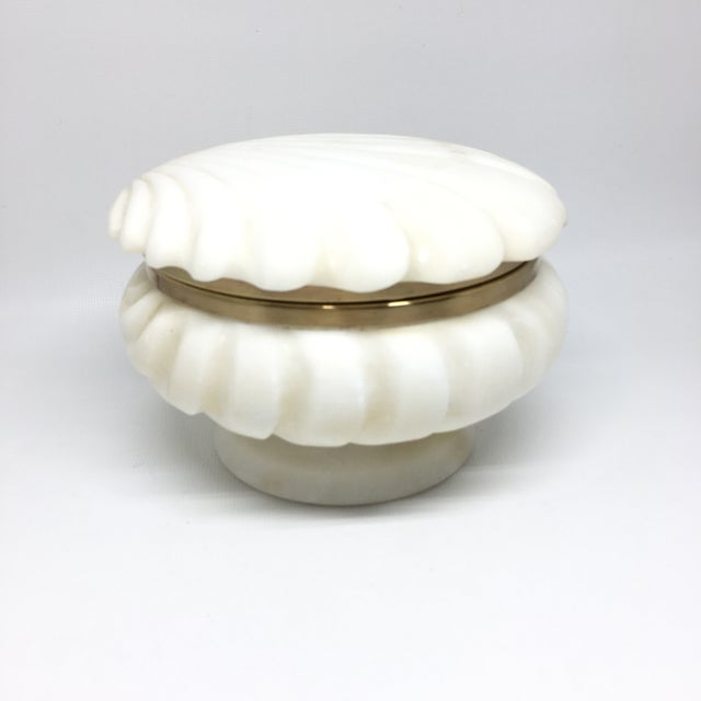 White alabaster and brass lidded box in shape of a shell. Brass is in excellent condition. Fully functional can be used as...