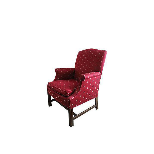 Pair of burgundy Chippendale wingback chairs with fleur de lis pattern and rolled arms. Mahogany Marlboro legs seat...