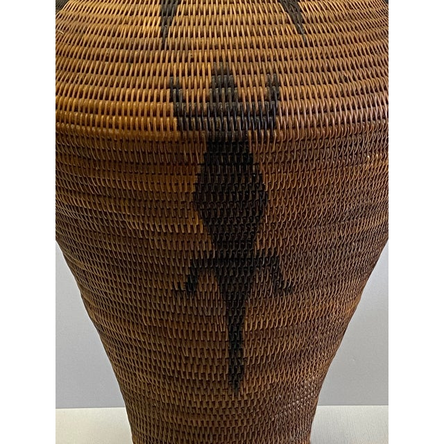 Great looking hand woven organic vintage urn shaped basket having decorative lid and tribal pattern with lizard.