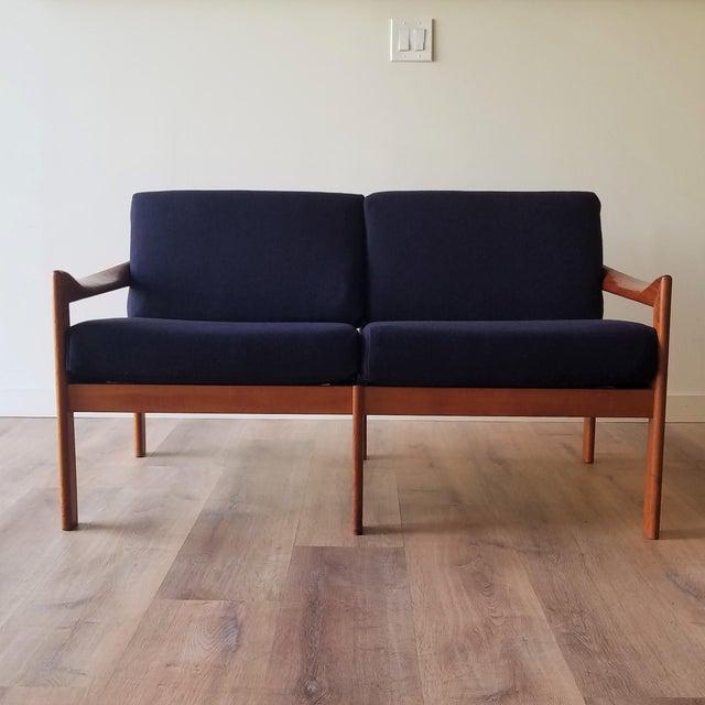Newly upholstered in a navy wool 1960s loveseat designed by Illum Wikkelsø for Niels Eilersen. The teak frame makes this...