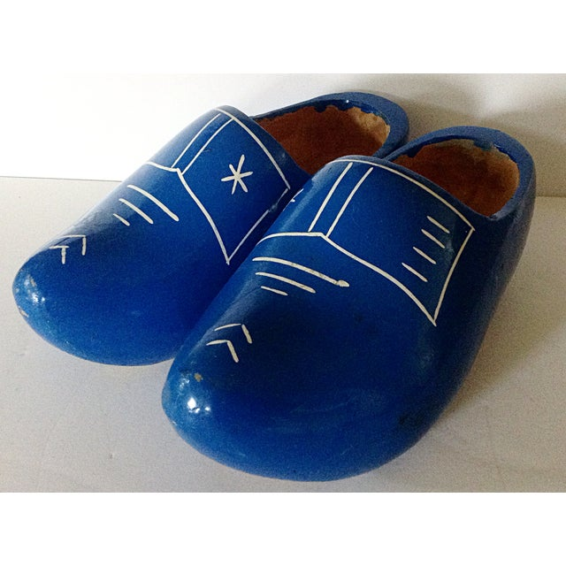 Darling pair of children's dutch wooden shoes in blue, with traditional white buckle design on top. There is a hole on the...