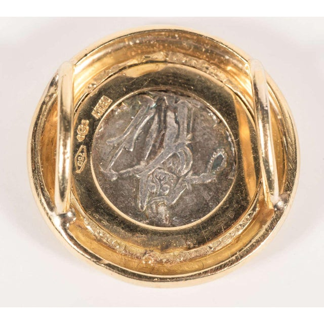 This ancient Roman coin is set in a 18k yellow gold slide with stepped ribbed detailing giving added dimension to the...