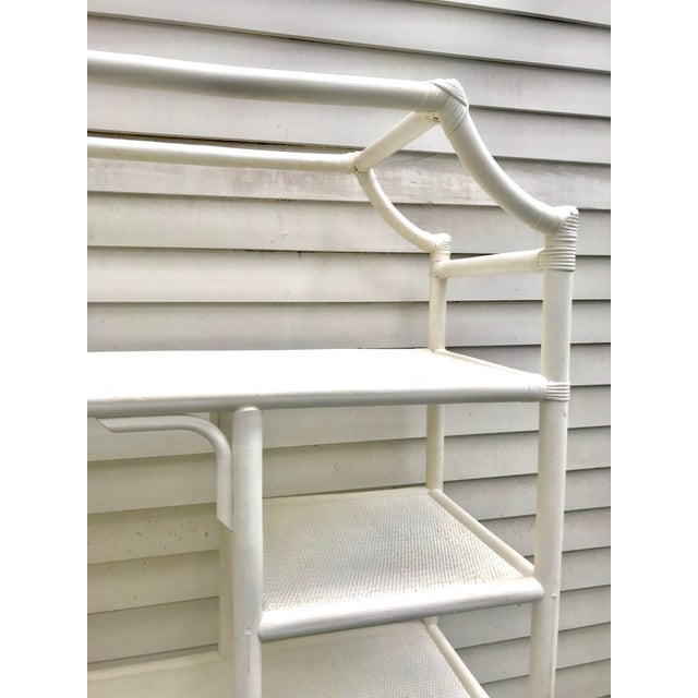 Fabulous vintage pagoda shaped shelving unit. In a Hollywood Regency style and made of rattan and each shelf lined in a...