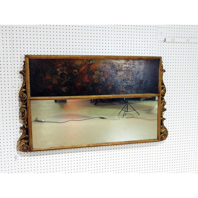 "Antique 19thC Regency style turmeau mirror with oil painting on top. The painting measures 11.5""h x 43""w. The mirror..."