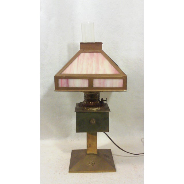 Antique style brass and pink slag glass lamp with ornate brass detailing and fittings in a hurricane style. The brass has...