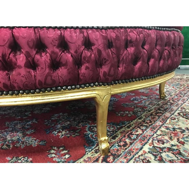 Five feet round Louis XIV style tufted ottoman. Has a wooden, gold painted base.