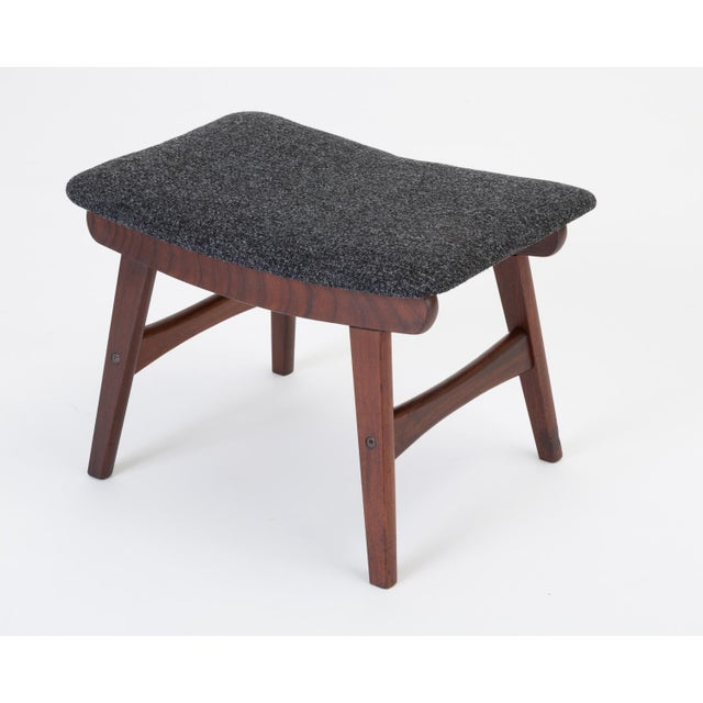 A modest Scandinavian ottoman or footrest has a base of teak wood with flat, angled legs and sculpted cross-supports. The...