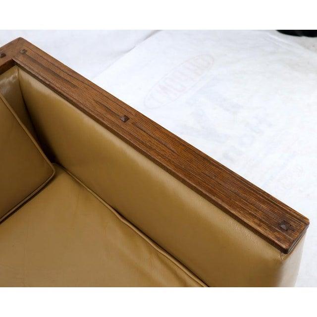 Oak frame tan supple leather upholstery Mid-Century Modern sofa. Artistic adze cut wood finishing technique presence detail.