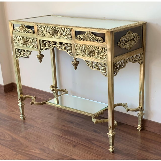 About The rectangular top with rounded corners and a mirror top, mounted with an oval foliate decorated swivel bronze...