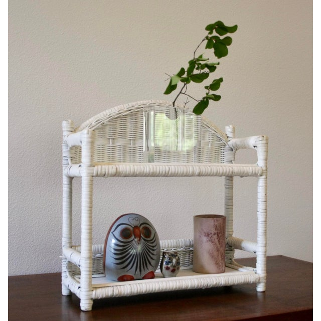 Sweet, slightly chippy white-painted wicker two-tier wall-mounted wall shelves. This piece is an adorable way to add a bit...